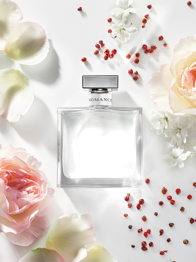 Bottle of Romance fragrance surrounded by flowers & pink peppercorns
